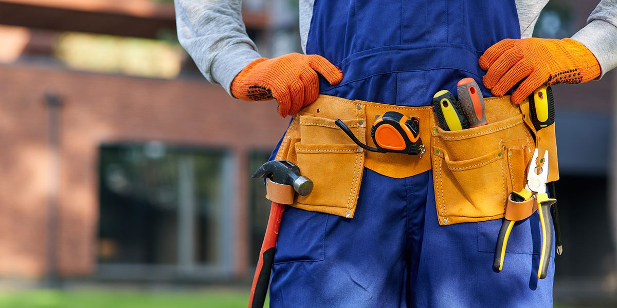 commercial property service male builder in blue overalls