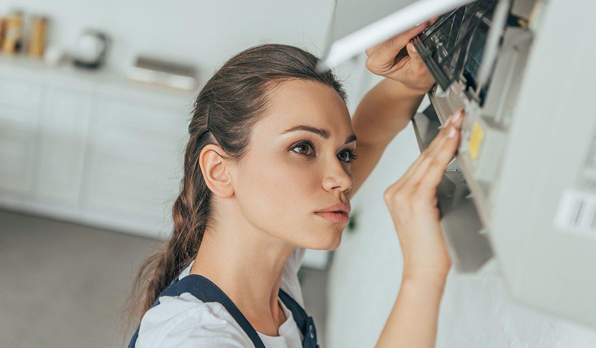 female worker repairing air conditioner