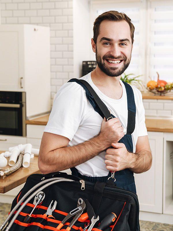 tradesman smiling and holding tool bag